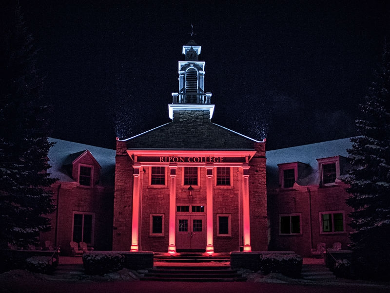 Harwood Memorial Union Porch lit up in red and blue at night