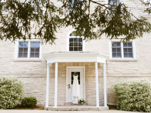 wedding dress hanging on the patio of a historic, brick building