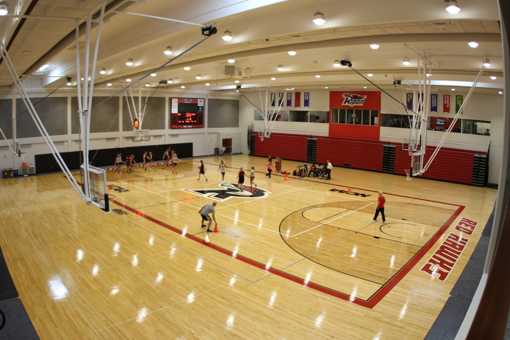 large gymnasium with students playing basketball